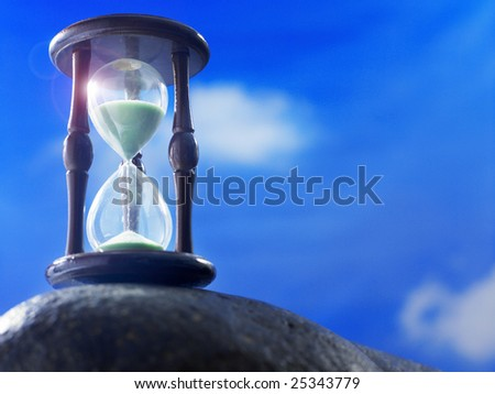 hourglass on the rock with blue sky as back ground