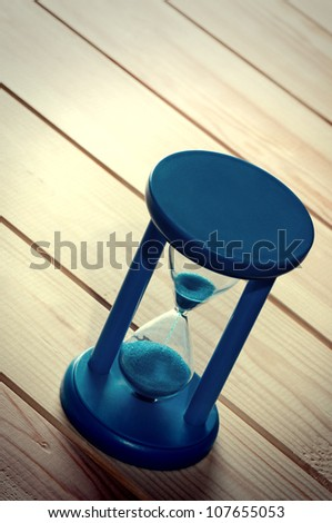 Hourglass on wooden boards.