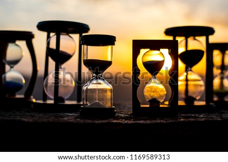 Hourglass Passing of Time Lapse Clouds. An hourglass in front of a bright blue sky with puffy white clouds passing. Time concept. Sunset time. Selective focus Stock photo ©