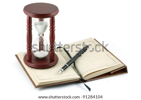 Hourglass, pen, notebook isolated on white background