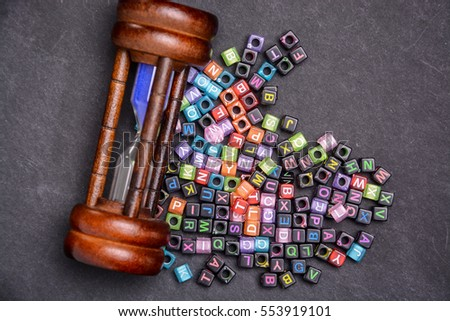 Hourglass sand timer and multicolor wording cube with wording TIME on black background. #553919101