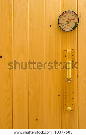 Hourglass, thermometer and hydrometer on wooden wall in sauna.