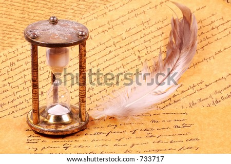 Hourglass with a feather and Parchments - stock photo