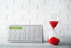 Hourglass with calender on brick wall background