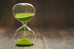 Hourglass with falling sand inside a glass bulb, passing time or lost time on a wooden background with space for text