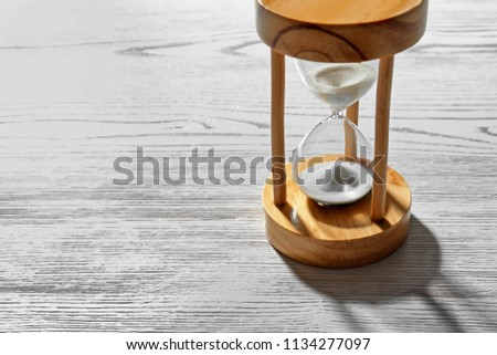 Hourglass with flowing sand on light wooden background. Time management