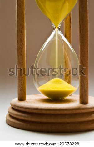 hourglass with yellow sand and shallow depth of field