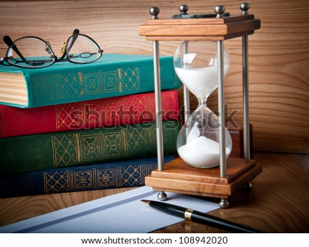 stock photo : Hourglasses and book on a wooden table