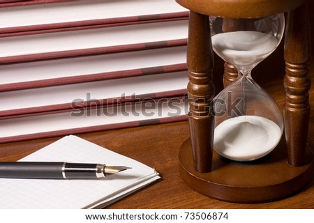 Hourglasses and book on a wooden table