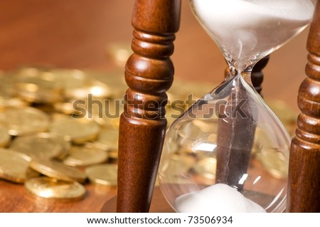 Hourglasses and coin On a wooden table