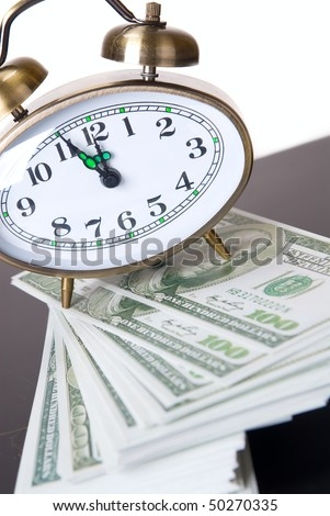 Hours an alarm clock on a background of American money