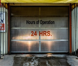 Hours of operation (24 hours) vinyl letter and number signage on a car wash with headlights shining through roll door. Wet pavement in foreground.