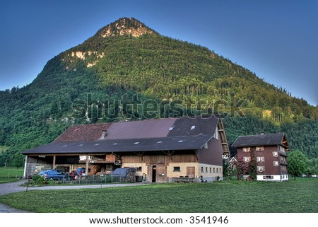 house and barn in Switzerland beneath a hill lit by morning light, HDRI