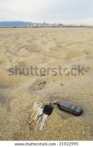 House and car keys with a remote left behind in the sand at the beach.