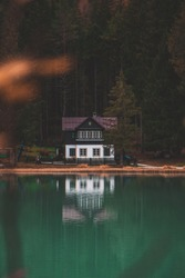 House and it's reflection on water with  forest