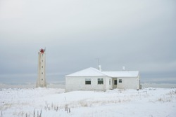House and lighthouse on winter day