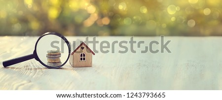 house and money. toy house, magnifying glass and coins. concept of mortgage, construction, rental housing. banner