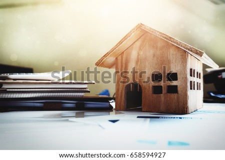 House and property for sale concept, wood house toy on office desk.