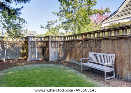 House back yard with wooden bench standing alone by the fence. Northwest, USA #493505143