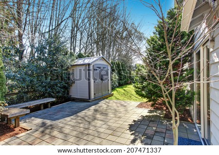 House backyard during summer. View of small shed and walkout deck