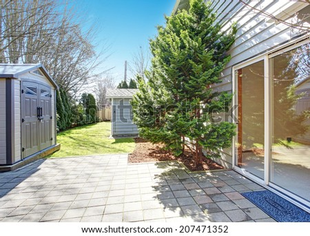 House backyard during summer. View of walkout deck and small shed
