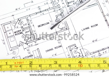 House blueprint with a measuring tape and a screwdriver on top of it - stock photo
