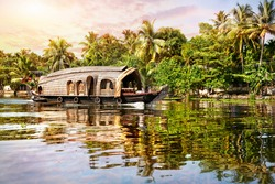 House boat in backwaters near palms at sunrise sky in Alappuzha, Kerala, India