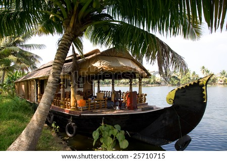 House boat in India over tropical palm on the river