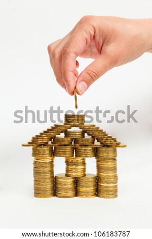 house built coins female hand on a light background, Front view