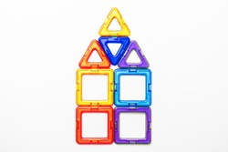 House built from the figures of a children magnetic constructor on white background.