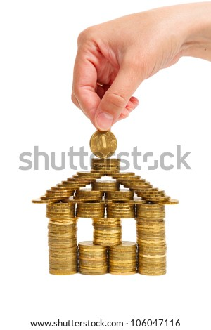 house built of coins female hand isolated on white background, front view