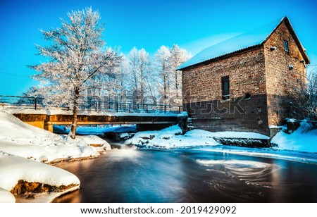 House by the river in winter snow time. Winter snow river house. Ice river in winter snow scene