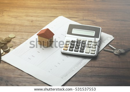 house,calculator and key on document