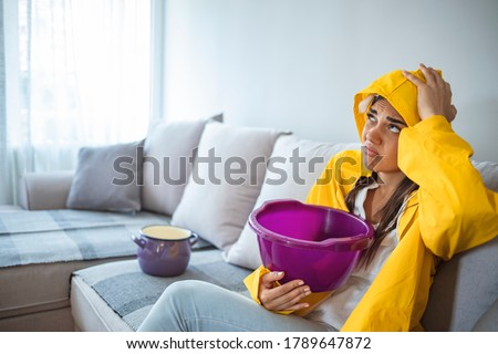 House Ceiling is Flowing - Woman in raincoat Holding Bucket While Water Droplets Leak From Ceiling. Shocked Woman Looks at the Ceiling While Collecting Water Which Leaks in the Living Room at Home.