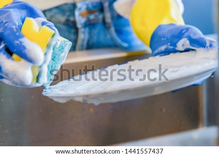 House chores - Washing the dishes on the kitchen sink - Blue and yellow plastic gloves with a lot of foam - Close-up #1441557437