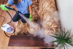 House cleaning. A girl in green gloves cleans the sofa and furniture with a steam generator. Cleaning service of the apartment. Blue T-shirt and young model. flat la. Strong vapor pressure.