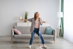 House cleaning with fun. Happy housewife singing her favorite song during cleanup, using mop as microphone, enjoying domestic work. Positive young maid tidying her home with pleasure
