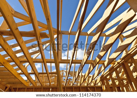 House construction with wood framing and roof trusses against a blue sky for your dream home.