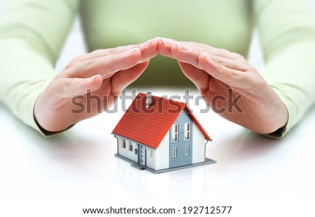 house covered of woman hands - protect and insurance real estate concept