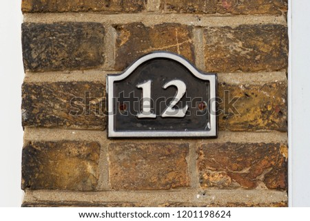 House door number 12 in white on black enamel, Twelve with a wavy roof you could call it