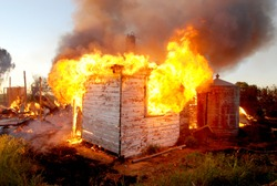 House engulfed in fire with most of the house burnt to the ground, and a corrugated iron tank in rural New South Wales Australia