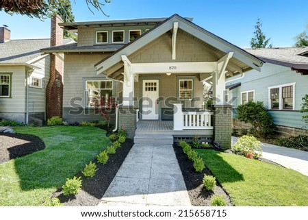 House entrance porch with white wooden door and white railings. Front yard landscape with walkway