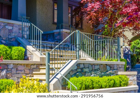 House entrance with nicely paved doorway, steps and handrails and trimmed and landscaped front yard.