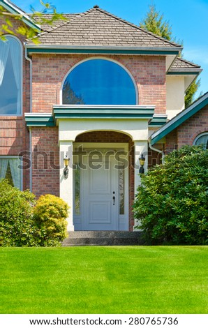 House entrance with nicely trimmed and landscaped front yard. Vertical.
