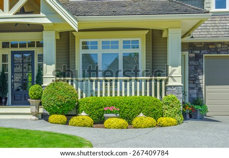 House entrance with porch and nicely trimmed and landscaped front yard.