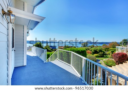 House exterior grey large porch with water view. - stock photo