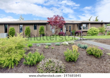 House exterior. View of entrance porch and front yard with lawn and flower bed
