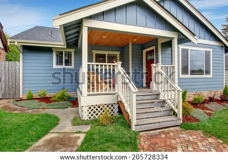 House exterior. View of front yard and small entrance porch with chairs