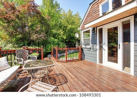 House exterior with large open deck and outdoor furniture.