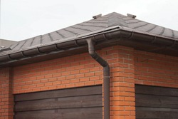 house facade made of red bricks and brown wooden planks under a tiled roof with a plastic drain pipe